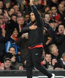 Manchester United's Carlos Tevez gestures to the fans whilst warming up on the touchline by touching the club badge on his training top