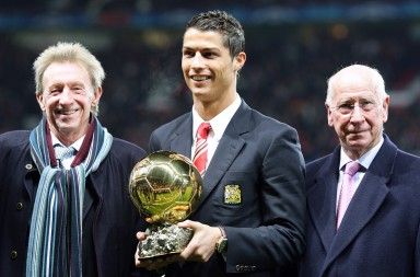 Manchester United's Cristiano Ronaldo poses with the Ballon d'Or before kick off alongside Denis Law (l) and Sir Bobby Charlton (r)
